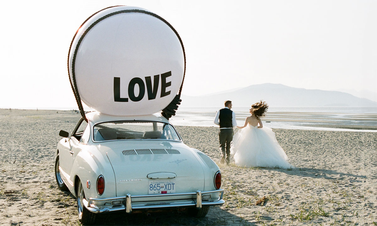 Newlyweds photographed on Vancouver beach with vintage Volkswagen Karmann Ghia and Big Love Ball | Photo by Sherri Koop